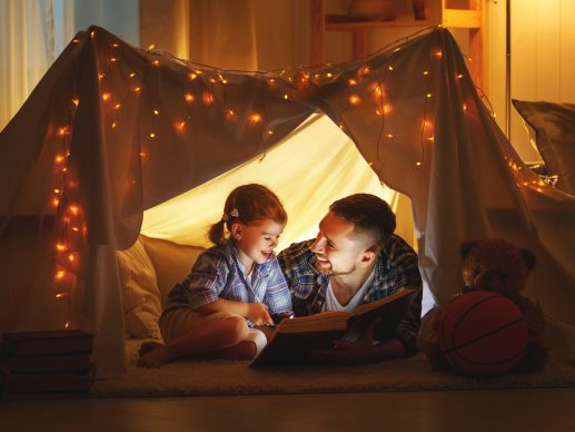 happy family father and child daughter  reading a book with a flashlight in a tent at home