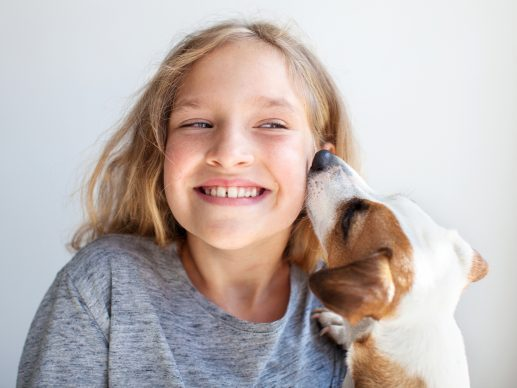Happy child with dog. Portrait girl with pet. Jack Rassell whispers a secret to teen